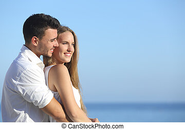 Attractive couple flirting and cuddling looking ahead with...