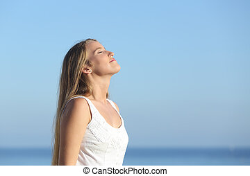 Beautiful blonde woman breathing happy with the blue sky in...