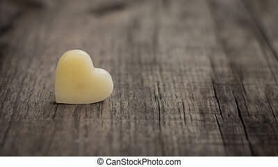 Wax heart - A beige heart out of wax on wooden background