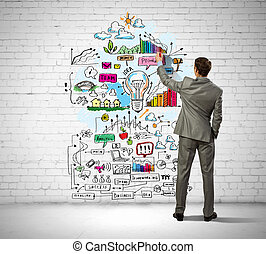 Businessman drawing sketches on wall - Back view image of...