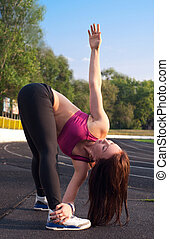 Stretching - Pretty sporty brawny strong, slim and fit young...