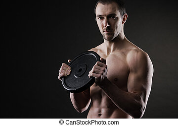 Bodybuilder - Muscular male athlete with a weight in hands
