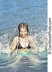 Girl splashing in lake - Young girl playing and splashing in...