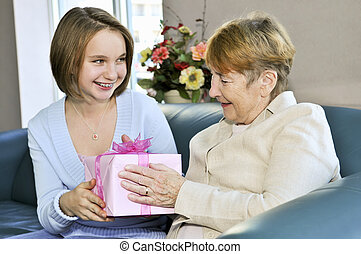 Granddaughter visiting grandmother - Granddaughter bringing...