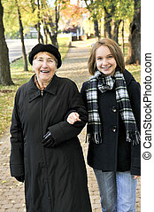 Granddaughter walking with grandmother - Teen granddaughter...