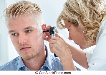 Medical exam - ENT physician looking into patients ear with...
