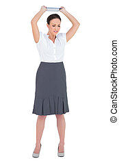 Angry businesswoman throwing her tablet pc while posing on...