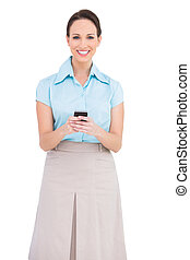 Happy classy young businesswoman sending text message while...