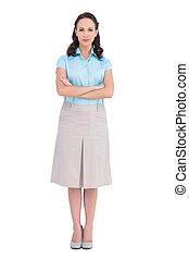 Unsmiling stylish businesswoman posing on white background