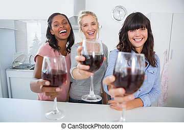 Cheerful friends toasting to the camera with glasses of red wine at home in kitchen