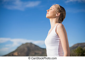 Blonde woman enjoying the sun against mountain on a sunny...
