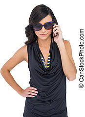 Serious elegant brunette wearing sunglasses on the phone on...