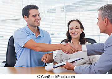 Handsome man with his wife shaking hands with estate agent...