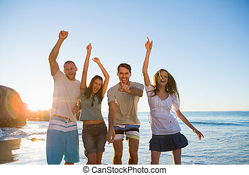 Cheerful group of friends dancing together on the beach