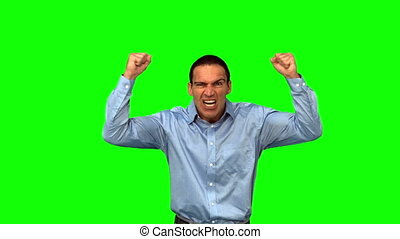 Angry businessman raising arms on green screen in slow...