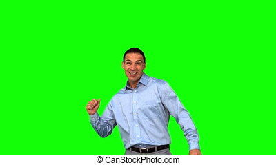Cheerful businessman raising his fist on green screen in...