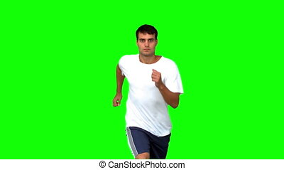 Handsome man jogging on green screen in slow motion