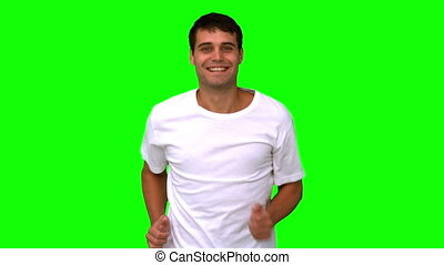 Man jogging on green screen in slow motion