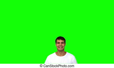 Cheerful man raising arms on green screen in slow motion