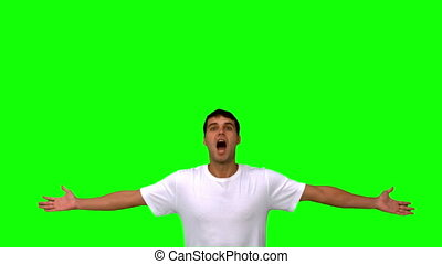 Handsome man jumping and raising arms on green screen in...