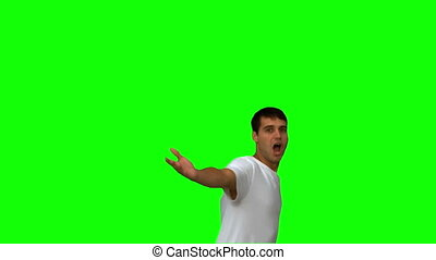 Handsome man turning and raising arms on green screen in...