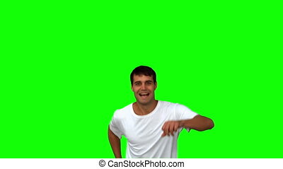 Handsome man giving thumbs up on green screen in slow motion