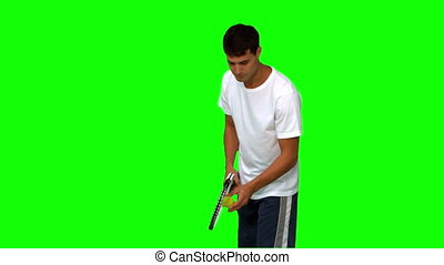 Man holding a tennis ball and a racquet on green screen in...