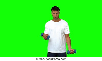 Handsome man lifting dumbbells on green screen in slow...