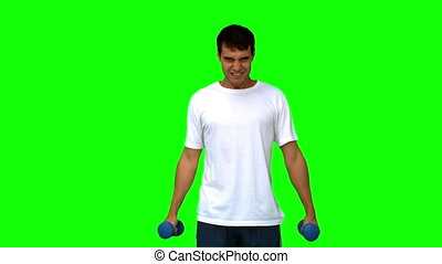 Attractive man lifting dumbbells on green screen in slow...