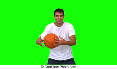 Man playing and dribbling with a basketball on green screen...