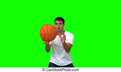 Man catching and throwing a basketball on green screen in...