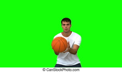 Handsome man catching and throwing a basketball on green...