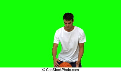 Man dribbling with a basketball on green screen in slow...