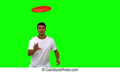 Man catching a frisbee on green screen in slow motion
