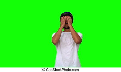 Man wearing a helmet holding his head on green screen in...