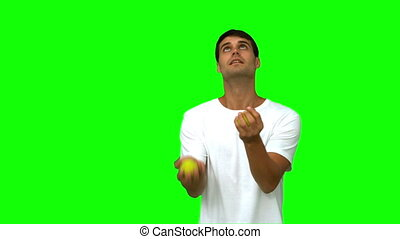 Handsome man juggling with balls on green screen in slow...