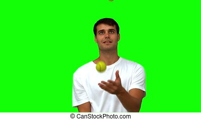 Man dribbling with tennis balls on green screen in slow...