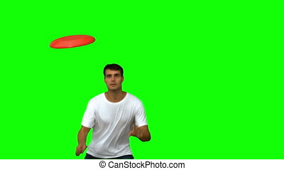 Man jumping and catching a frisbee on green screen in slow...