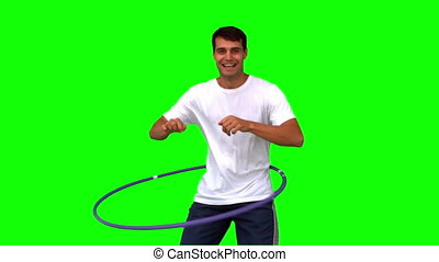 Man playing with a hula hoop on green screen in slow motion