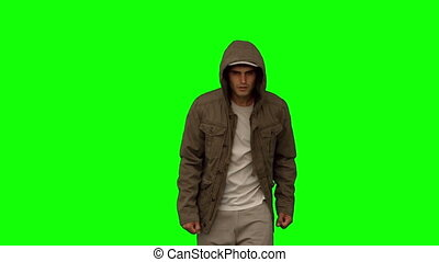 Man with a coat walking toward camera on green screen in...