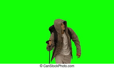 Attractive man with a coat trekking on green screen in slow...