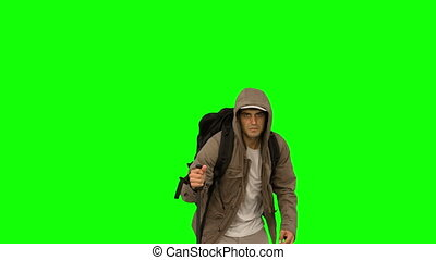 Man with a coat and a hiking stick running on green screen...