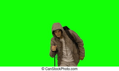 handsome man with a coat trekking on green screen in slow...