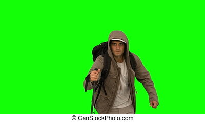 Man with a hiking stick running on green screen in slow...