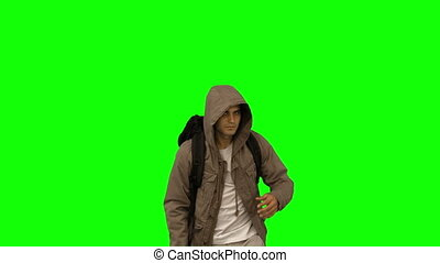 Handsome man walking towards the camera on green screen in...
