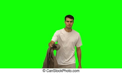 Handsome man holding his coat on green screen in slow motion