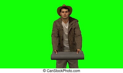 Man rolling out a sleeping bag on green screen in slow...