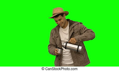 Man pouring coffee from a vacuum flask on green screen in...