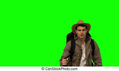 Man with a hat walking under leaves falling on green screen...