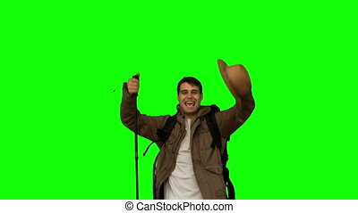 Happy man throwing his hat on green screen in slow motion